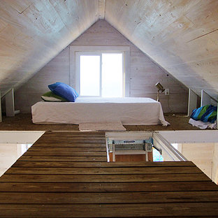 Small beach style loft-style bedroom in Other with beige walls and medium hardwood floors.