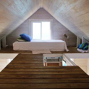 Modelo de dormitorio tipo loft, costero, pequeño, con paredes beige y suelo de madera en tonos medios