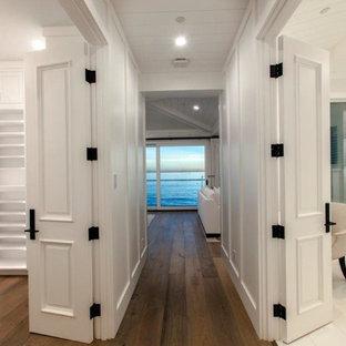 Foto di una grande camera matrimoniale stile marino con pareti bianche, parquet scuro, camino classico, cornice del camino in pietra e pavimento marrone