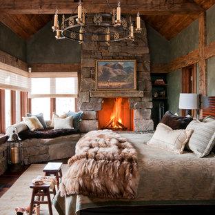 Foto de habitación de invitados rural con chimenea tradicional, marco de chimenea de piedra, paredes verdes y moqueta