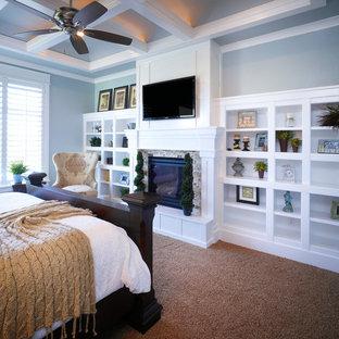 На фото: хозяйская спальня среднего размера в классическом стиле с синими стенами, ковровым покрытием, стандартным камином, фасадом камина из камня и коричневым полом с