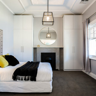 This is an example of a contemporary bedroom in Adelaide with grey walls, carpet, grey floor and a standard fireplace.