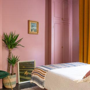 Foto de habitación de invitados bohemia, de tamaño medio, sin chimenea, con paredes rosas, suelo de madera oscura y suelo marrón