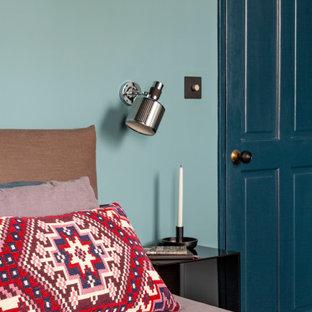 Ejemplo de dormitorio principal, ecléctico, de tamaño medio, sin chimenea, con paredes azules, suelo de madera oscura y suelo marrón