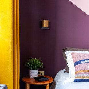 Imagen de habitación de invitados bohemia, de tamaño medio, sin chimenea, con paredes rosas, suelo de madera oscura y suelo marrón