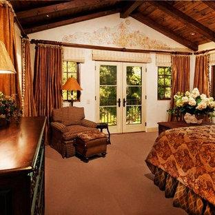 Foto de dormitorio principal, mediterráneo, grande, con paredes beige, suelo de piedra caliza, marco de chimenea de piedra y suelo beige