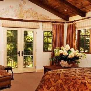 Diseño de dormitorio principal, mediterráneo, grande, con paredes beige, suelo de piedra caliza, marco de chimenea de piedra y suelo beige