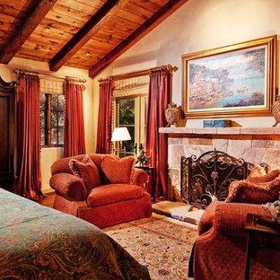 Imagen de dormitorio principal, mediterráneo, grande, con marco de chimenea de piedra, paredes beige, suelo de piedra caliza y suelo beige