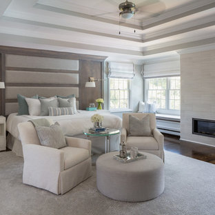Inspiration for a huge transitional master medium tone wood floor and brown floor bedroom remodel in New York with gray walls, a standard fireplace and a tile fireplace