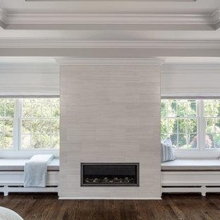 Diseño de dormitorio principal, clásico renovado, extra grande, con paredes grises, suelo de madera en tonos medios, chimenea tradicional, marco de chimenea de baldosas y/o azulejos y suelo marrón
