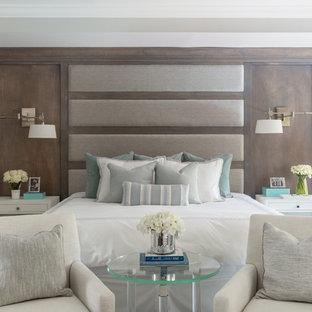 Immagine di un'ampia camera matrimoniale classica con pareti grigie, pavimento in legno massello medio, camino classico, cornice del camino piastrellata e pavimento marrone