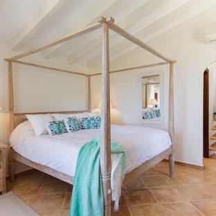 マヨルカ島の中サイズの地中海スタイルのおしゃれな主寝室 (白い壁、テラコッタタイルの床、暖炉なし) のインテリア