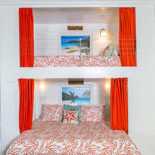 Inredning av ett maritimt mycket stort sovloft, med vita väggar, travertin golv och beiget golv