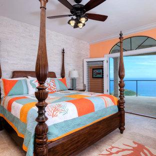 Modelo de habitación de invitados tropical, grande, con parades naranjas, suelo de travertino y suelo beige