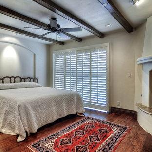オレンジカウンティの大きい地中海スタイルのおしゃれなゲスト用寝室 (コーナー設置型暖炉、白い壁、濃色無垢フローリング、漆喰の暖炉まわり、茶色い床) のレイアウト