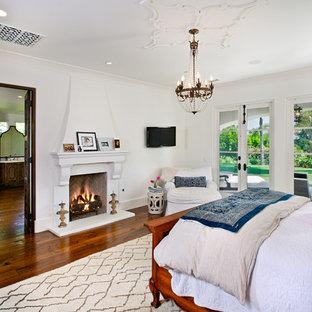 Esempio di una camera da letto mediterranea con pareti bianche, parquet scuro e camino classico