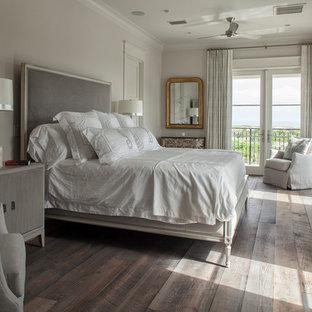 Ispirazione per una grande camera matrimoniale costiera con pareti bianche, pavimento in legno verniciato, camino classico, cornice del camino in pietra e pavimento marrone