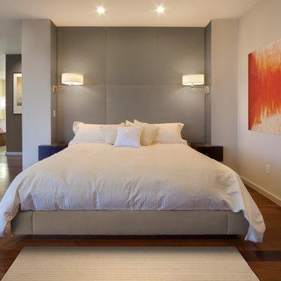 Example of a minimalist medium tone wood floor bedroom design in Orlando with white walls