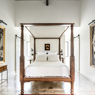 Inspiration for a small industrial loft-style bedroom in Houston with white walls and concrete floors.