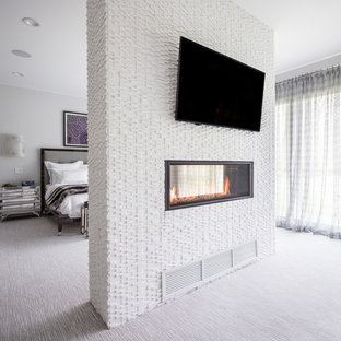 Example of an eclectic carpeted and gray floor bedroom design in New York with white walls, a two-sided fireplace and a stone fireplace