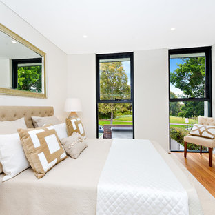 Design ideas for a traditional bedroom in Sydney with white walls and light hardwood floors.