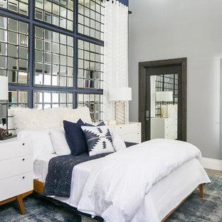 Bedroom - mid-sized modern guest medium tone wood floor and gray floor bedroom idea in San Diego with blue walls