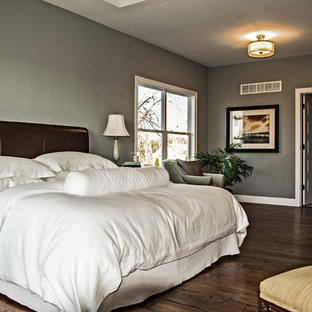 This is an example of a mid-sized arts and crafts master bedroom in St Louis with grey walls, medium hardwood floors, no fireplace and brown floor.