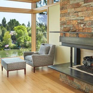 Diseño de dormitorio moderno, de tamaño medio, con chimenea de esquina, marco de chimenea de metal y suelo de madera clara