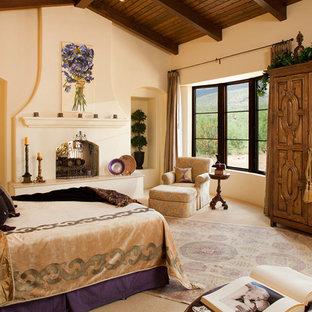 フェニックスのサンタフェスタイルのおしゃれな寝室 (両方向型暖炉)