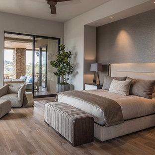 Foto de dormitorio principal, actual, grande, con paredes beige, suelo de madera en tonos medios, chimenea lineal, marco de chimenea de hormigón y suelo beige