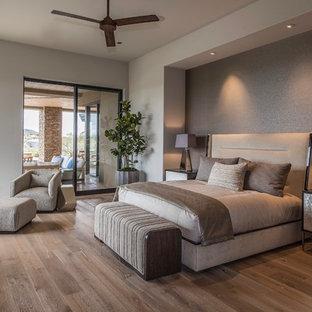 フェニックスの広いコンテンポラリースタイルのおしゃれな主寝室 (無垢フローリング、グレーの壁、茶色い床) のレイアウト