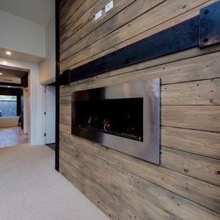 Foto de dormitorio principal, clásico renovado, extra grande, con paredes grises, moqueta, chimeneas suspendidas, marco de chimenea de metal y suelo beige