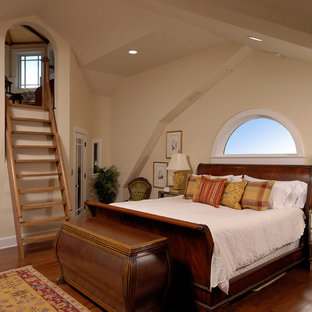 This is an example of a traditional loft-style bedroom in DC Metro with beige walls and medium hardwood floors.