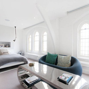Photo of a contemporary master bedroom in London with white walls and carpet.