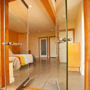 Diseño de dormitorio contemporáneo con suelo de cemento y paredes blancas