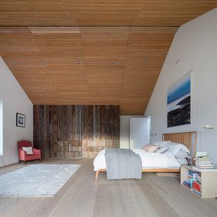 Diseño de dormitorio principal, marinero, extra grande, con paredes blancas, suelo de madera clara, marco de chimenea de madera y suelo gris