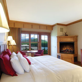 Foto di una piccola camera degli ospiti stile americano con pareti beige, moquette, camino ad angolo, cornice del camino in legno e pavimento beige