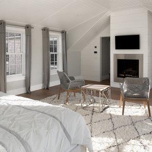 Diseño de dormitorio principal, costero, grande, con paredes grises, suelo de madera clara, chimeneas suspendidas y marco de chimenea de metal
