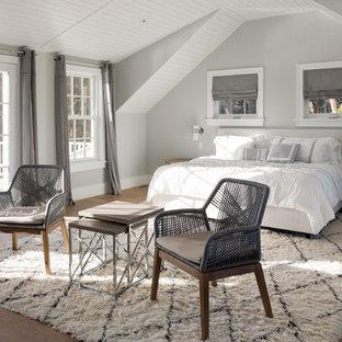 Großes Maritimes Hauptschlafzimmer mit grauer Wandfarbe, hellem Holzboden, Hängekamin und Kaminumrandung aus Metall in Boston