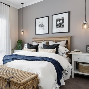 Photo of a beach style bedroom in Other with beige walls, carpet and brown floor.