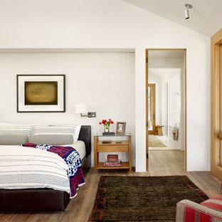 Bedroom - country master medium tone wood floor and brown floor bedroom idea in Austin with white walls