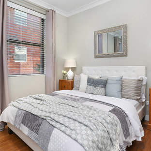 This is an example of a transitional master bedroom in Sydney with grey walls and medium hardwood floors.