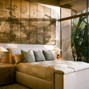 Design ideas for a medium sized world-inspired master bedroom in Los Angeles with beige walls, carpet, a two-sided fireplace, a tiled fireplace surround and multi-coloured floors.