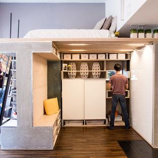 Ispirazione per una piccola camera da letto stile loft industriale con pareti grigie, pavimento in legno massello medio e nessun camino