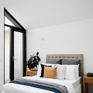 Photo of a small contemporary master bedroom in Melbourne with white walls, light hardwood floors and brown floor.