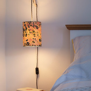 デヴォンの中くらいのおしゃれな主寝室 (白い壁、塗装フローリング、標準型暖炉、木材の暖炉まわり、グレーの床) のインテリア