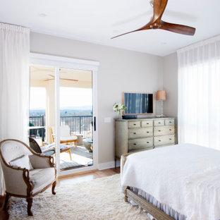 Cette image montre une chambre parentale traditionnelle de taille moyenne avec un mur beige, un sol en bois clair, aucune cheminée et un sol multicolore.