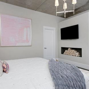 Diseño de dormitorio principal, contemporáneo, de tamaño medio, con paredes multicolor, chimenea tradicional, marco de chimenea de metal y suelo negro