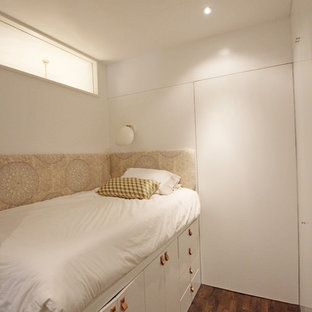 Photo of a small mediterranean loft-style bedroom in New York with white walls and medium hardwood floors.