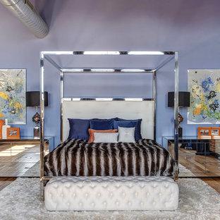 Foto di una camera da letto stile loft minimal con pareti viola, pavimento in legno massello medio e nessun camino
